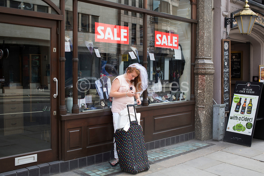 Bride to be on her hen party texting her friends as she waiting outside a suit shop with a sale on, to meet them for her big day out in London, England, United Kingdom. (photo by Mike Kemp/In Pictures via Getty Images)