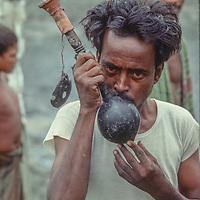Homeless village people from Bangladesh smoke a homemade hookah at  Mirpur Destitute Ramp near Dhaka, Bangladesh.  1977. They were left destitute by a back to back cyclone and  brutal war of independence in 1971.   1977 image.