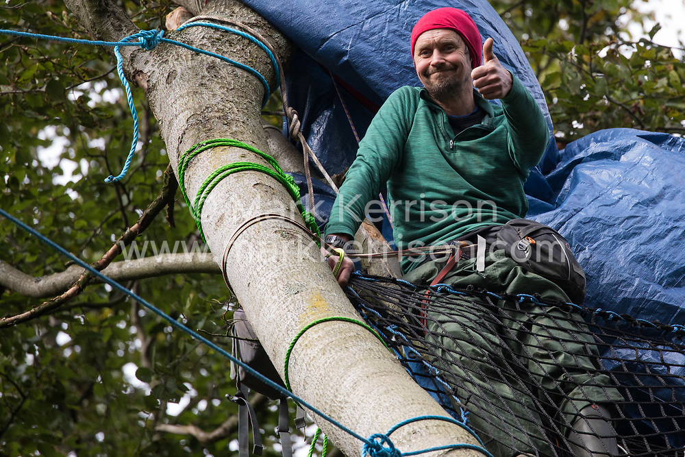 Daniel Marc Hooper, better known as environmental activist Swampy, gives a thumbs up from a makeshift tree house about sixty feet above ground at a wildlife protection camp in ancient woodland at Jones' Hill Wood on 5 October 2020 in Aylesbury Vale, United Kingdom. The Jones' Hill Wood camp, one of several protest camps set up by anti-HS2 activists along the route of the £106bn HS2 high-speed rail link in order to resist the controversial infrastructure project, is currently being evicted by National Eviction Team bailiffs working on behalf of HS2 Ltd.