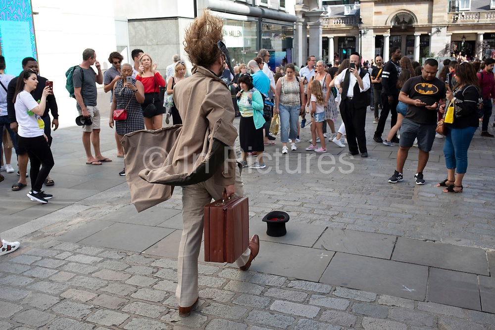 Living statue street performer as a commuter walking in the wind with hair and clothes billowing as passers by look on in Covent Garden in London, United Kingdom.