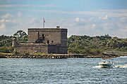 A pleasure craft passes Fort Matanzas National Monument in St Augustine, Florida. The stone coastal fort was built in 1742 by the Spanish to guard the Matanzas Inlet.