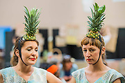Performers with pineapples on their heads iteract with visitors in the cafe - The Turbine Festival 2015 - One City One Day - sponsored by Hyundai. The festival includes many activities for all ages exploring art and technology. The hall is decorated with giant white streamers.