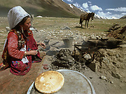 """A Kyrgyz woman bakes Nan bread in dung fire outside in front of her yurt.<br /> Kara Jelgha (""""black valley"""") summer camp. The campment of Abdul Rashid Khan, the king of the Kyrgyz.<br /> <br /> Adventure through the Afghan Pamir mountains, among the Afghan Kyrgyz and into Pakistan's Karakoram mountains. July/August 2005. Afghanistan / Pakistan."""