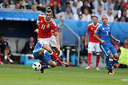 Gareth Bale of Wales breaks away from a Slovakian tackler. Euro 2016, Wales v Slovakia at Matmut Atlantique , Nouveau Stade de Bordeaux  in Bordeaux, France on Saturday 11th June 2016, pic by  Andrew Orchard, Andrew Orchard sports photography.