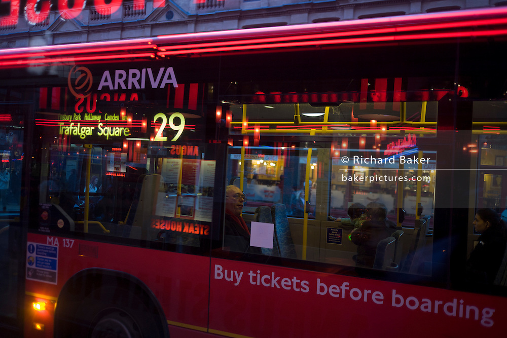 Commuters on number 29 red bus at stop in Charing Cross Road in central London.