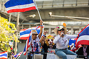"""15 JANUARY 2014 - BANGKOK, THAILAND:  Anti-government protestors in Bangkok motorcade through a residential neighborhood near Sukhumvit Road. Tens of thousands of Thai anti-government protestors continued to block the streets of Bangkok Wednesday to shut down the Thai capitol. The protest, """"Shutdown Bangkok,"""" is expected to last at least a week. Shutdown Bangkok is organized by People's Democratic Reform Committee (PRDC). It's a continuation of protests that started in early November. There have been shootings almost every night at different protests sites around Bangkok. The malls in Bangkok are still open but many other businesses are closed and mass transit is swamped with both protestors and people who had to use mass transit because the roads were blocked.   PHOTO BY JACK KURTZ"""