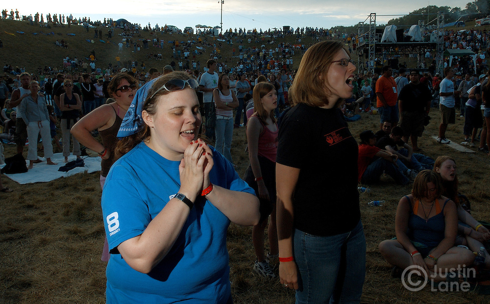 Two women sing along to a worship song during a concert at the 2005 Cornerstone Festival in Bushnell, IL. The festival, which began in 1984, features Christian musicians from across the country and is attended by thousands of people.
