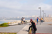 woman cycles on the Eurovelo 1 Atlantic coast route Near Vila Nova de Gaia and Porto, Portugal. The Atlantic coast on the left