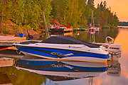 Boat and docks at Star Lake at sunrise. Cottage Country Living.<br />Whiteshell Provincial Park<br />Manitoba<br />Canada