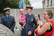 On the 100th anniversary of the Royal Air Force RAF and following a flypast of 100 aircraft formations representing Britains air defence history which flew over central London, a serviceman holds his child next to the memorial to those killed in the 2002 Bali bombing, on 10th July 2018, in London, England.