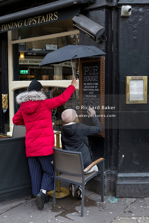 Sheltered by an umbrella held above her head, a woman signwriter artist paints the text of a West End pub's food menu of pies and fish & chips, outside The Porcupine, a traditional British pub on Charing Cross Road, on 17th February 2020, in London, England.