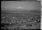 Ackroyd 02104-1. aerial of North Portland looking east and south to Mt. Hood. Albina rail yards and area north of Broadway Bridge in foreground. (scratches). March 29, 1950