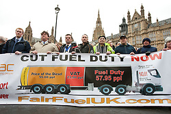 © licensed to London News Pictures. London, UK 07/03/2012. Members of  the FairFuel protest group hold a banner as they lobby outside the Houses of the Parliaments after handing in their report to Downing Street. Photo credit: Tolga Akmen/LNP
