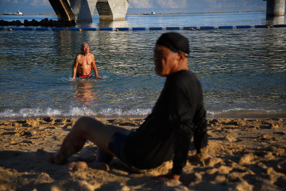 Ninety-one-year-old Fumiyasu Yamakawa sits on the beach during his morning exercises near his home in Naha, Okinawa.