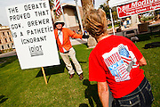 22 OCTOBER 2010 - PHOENIX, AZ:  BILL DEMSKI, from Glendale, AZ, and an opponent of the Tea Party, argues with a Tea Party supporter about Arizona Gov Jan Brewer, a favorite of the Arizona Tea Party because of her tough stand on illegal immigration at a Tea Party rally in Phoenix. About 300 people attended a Tea Party rally on the lawn of the Arizona State Capitol in Phoenix Friday. They demanded lower taxes, less government spending, repeal of the health care reform bill, and strengthening of the US side of the US - Mexican border. They listened to Arizona politicians and applauded wildly when former Alaska Governor Sarah Palin and her son, Trig, made a surprise appearance. The event was a part of the Tea Party Express bus tour that is crossing the United States.     Photo by Jack Kurtz