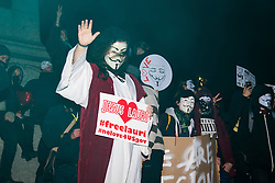 """London, November 5th 2016. Anti-capitalists and anarchists participate in the Million Mask March, an annual event that happens on November 5th each year in cities across the world, as part of a protest against the establishment. Many of the protesters wear Guy Fawkes masks, often associated with the internet activism group Anonymous. PICTURED: """"Jesus"""" poses on the plinth of Nelson's Column in Trafalgar Square."""