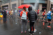 People under a red umbrella watching participants taking part in the London Marathon on 28th April 2019 in London, England, United Kingdom. The London Marathon, presently known through sponsorship as the Virgin Money London Marathon, is a long-distance running event. The event was first run in 1981 and has been held in the spring of every year since. The race is mainly known for ebing a public race where ordinary people can challenge themsleves while raising great amounts of money for various charities.