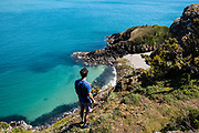 Man stood on the cliff edge looking down towards Vicard Harbour, a tiny cove surrounded by calm clear water on the north coast of Jersey, CI