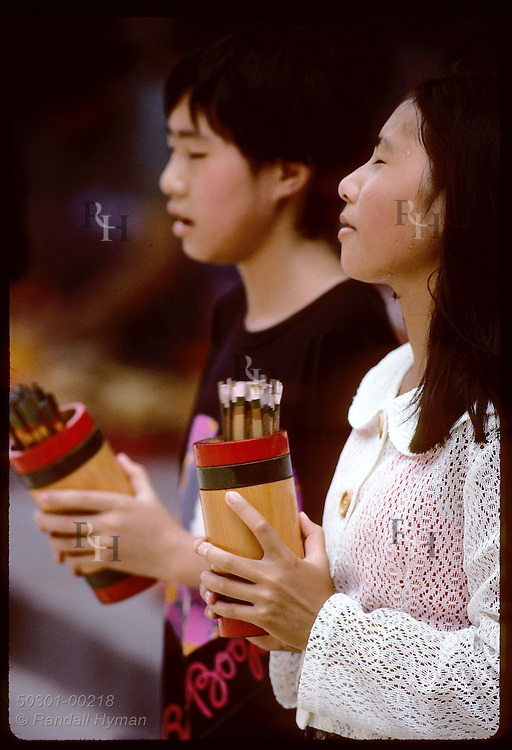 Kids shake cups of 'chim' sticks to get lucky number & have them interpreted;Wong Tai Sin/Kowloon Hong Kong