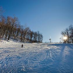 Skiers at Jiminy Peak ski resort in the Berkshire Mountains in Hancock, Massachusetts.  Wind turbine.