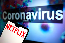 A Netflix logo seen displayed on a mobile phone with an illustrative model of the Coronavirus displayed on a monitor in the background. Photo credit should read: James Warwick/EMPICS Entertainment