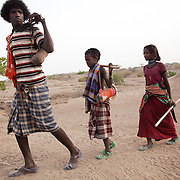 Big brother, 16 year old Muhammed and his siblings Hussein and Rabia head off to rejoin with their mother and the heard of goats. They have been to drink water and water their goats from water in a hole dug into a dried up river bed. It's dry season in Afar and water is hard to come by. Both animals and humans suffer in the dry season and travel long distances to find water and grassing.  Action for Integrated Sustainable Development Association (AISDA) work in the AFAR region of Eastern Ethiopia, based in Delafagi. The Afars practise an old tradition of Female Genital Mutilation where the baby girls has her clitoris and labia cut away and her vagina sewn up. The day before her wedding day the girl is un-stiched ready for marriage. Its a brutal and barbaric tradition which AISDA is challenging with great effect, now more than a hundred girls in Dowe district have been saved from the knife and AISDA is now rolling out the scheme in Delafagi. Delafagi is where the oldest ever human remains have been found, the found is thought to be 4.5 mill years old.