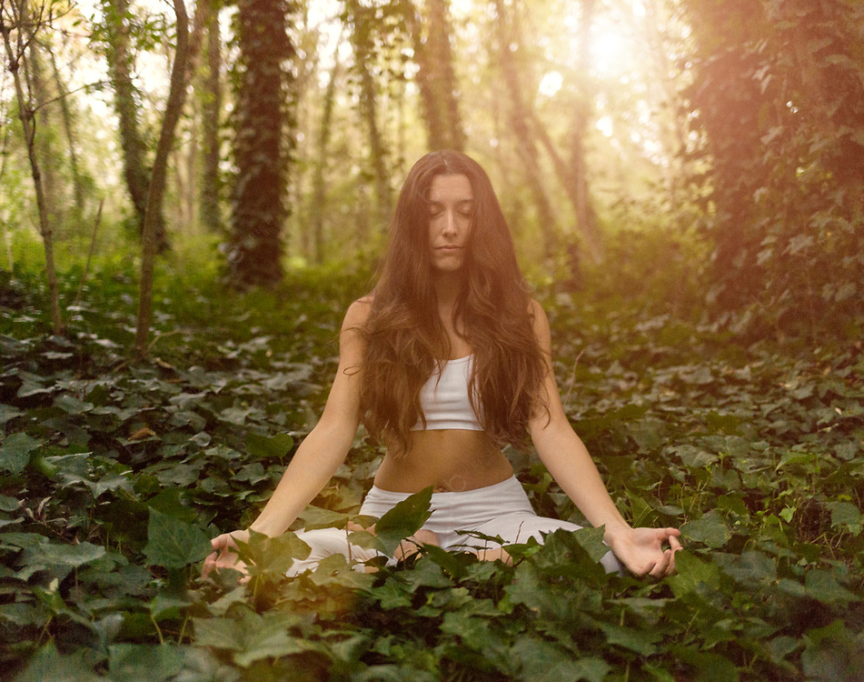 Woman doing yoga meditation in forest