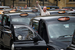 © London News Pictures. 17/07/2012. London, UK.  A Black Cab driver gestures to the camera as taxi drivers block up Parliament Square in Westminster, London on July 17, 2012 to demonstrate against not being allowed to use the official Olympic lanes during the London Olympic Games. Photo credit: Ben Cawthra/LNP.