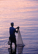 silhouette of man fishing with net at sunset
