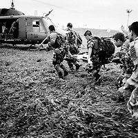 A wounded Government soldier is carried by his collegues to a medivac helicopter. Two of his companions who were killed earlier when a FARC planted bomb exploded in a bus they were searching. The bus was part of a roadblock built to facilitate the kidnap of Ingrid Betancourt on the 23rd February.<br />