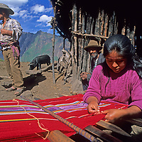 A young woman weaves on a backstrap loom at her family's homestead in Peru's Cordillera Vilcabamba.