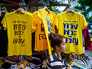 "03 JULY 2018 - BANGKOK, THAILAND: A vender in Bobae Market in Bangkok sells yellow tee shirts that save ""Long Live the King."" The birthday of King Maha Vajiralongkorn Bodindradebayavarangkun, Rama X, is 28 July. The King, the only son of Thailand's late King Bhumibol Adulyadej, became the King of Thailand in 2016 after the death of his father. King Vajiralongkorn was born on 28 July 1952, a Monday. In Thai culture each day of the week has a color, and yellow is the color is associated with Monday, so people wear yellow for the month before his birthday to honor His Majesty.    PHOTO BY JACK KURTZ"