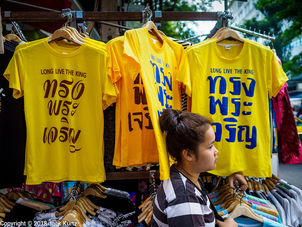 """03 JULY 2018 - BANGKOK, THAILAND: A vender in Bobae Market in Bangkok sells yellow tee shirts that save """"Long Live the King."""" The birthday of King Maha Vajiralongkorn Bodindradebayavarangkun, Rama X, is 28 July. The King, the only son of Thailand's late King Bhumibol Adulyadej, became the King of Thailand in 2016 after the death of his father. King Vajiralongkorn was born on 28 July 1952, a Monday. In Thai culture each day of the week has a color, and yellow is the color is associated with Monday, so people wear yellow for the month before his birthday to honor His Majesty.    PHOTO BY JACK KURTZ"""