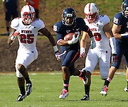 Oct. 22, 2011 - Charlottesville, Virginia - USA; Virginia Cavaliers running back Khalek Shepherd (38) runs past North Carolina State Wolfpack safety Dontae Johnson (25) and North Carolina State Wolfpack safety Brandan Bishop (30) during an NCAA football game at the Scott Stadium. NC State defeated Virginia 28-14. (Credit Image: © Andrew Shurtleff