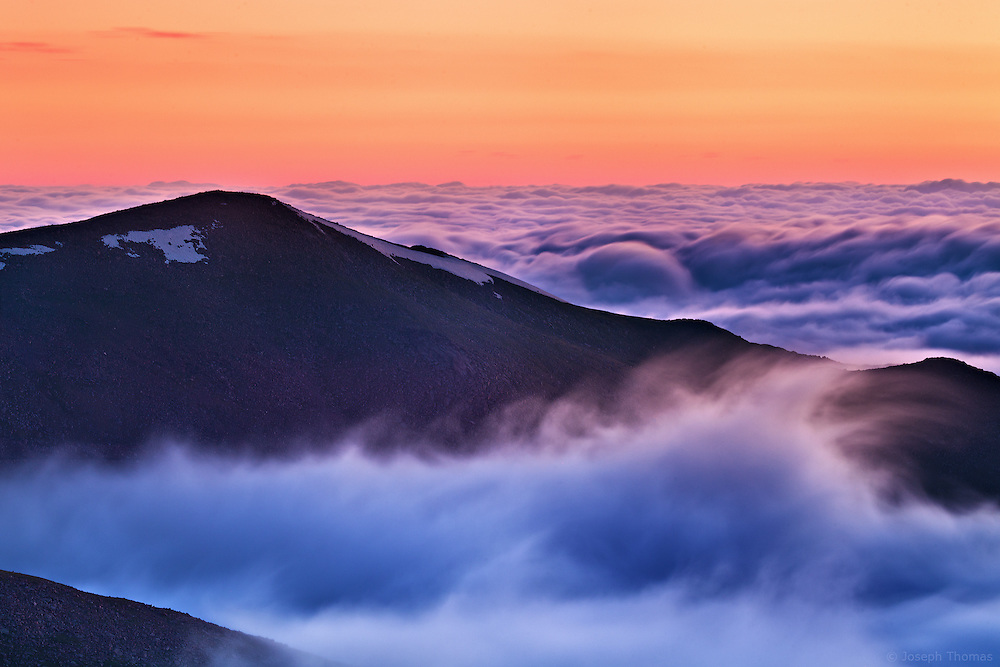 Swelling tides of undulant clouds break against The Continental Divide like mighty ocean waves. Rogers Peak, Colorado.