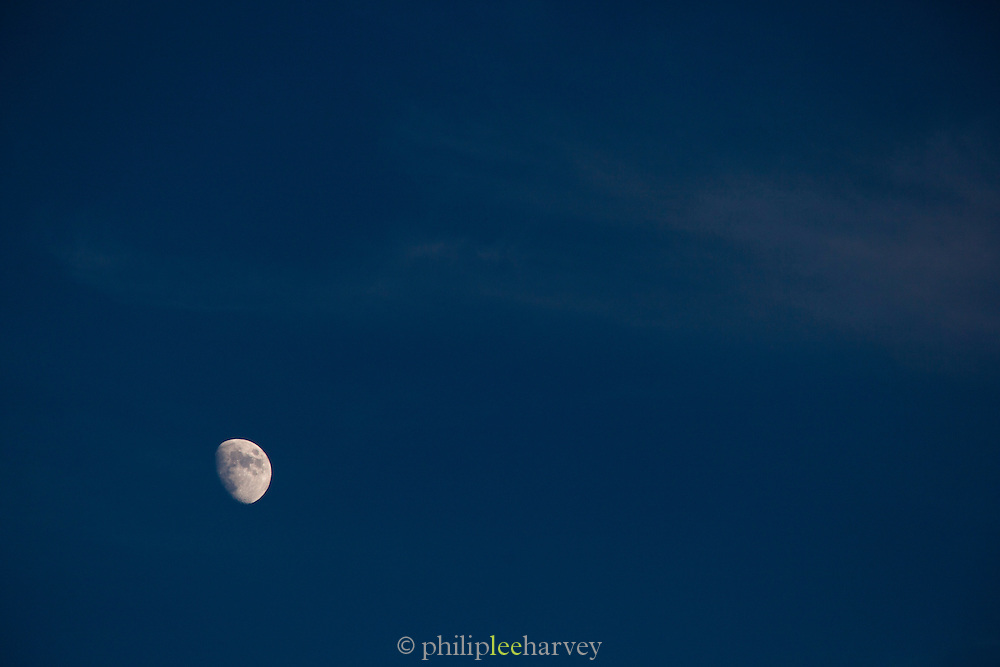 The moon seen at dusk in the capital city of Lisbon, Portugal