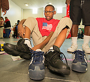 A student tries on his new shoes during the Hilliard Fall Festival, October 24, 2013. Free shoes were distributed to all the students and parents were able to sign up for services and receive books and backpacks for their children.