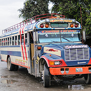 A chicken bus behind the Mercado Municipal (town market) in Antigua, Guatemala. From this extensive central bus interchange the routes radiate out across Guatemala. Often brightly painted, the chicken buses are retrofitted American school buses and provide a cheap mode of transport throughout the country.