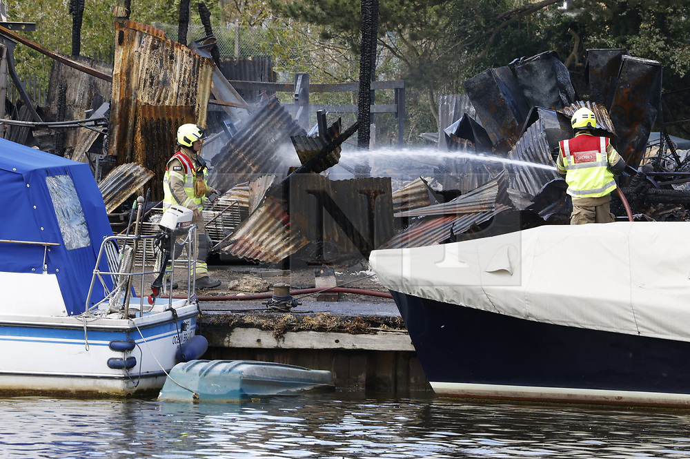 © Licensed to London News Pictures. 04/05/2021. London, UK. Fire fighters continue to damp down the remains of two boatyards on Platt's Eyot, an island on The River Thames in south west London. It is being reported that a Dunkirk Little Ship The Lady Gay was damaged in the fire as it was on a slipway at the yard. Photo credit: Peter Macdiarmid/LNP