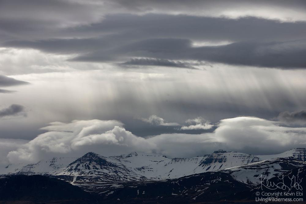 The sun shines through heavy storm clouds over Skarðsheiði, a 1041 meter (3415 feet) mountain range near Borgarnes, Iceland.