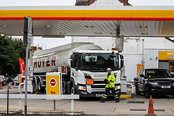 Licensed to London News Pictures. 25/09/2021. London, UK. A Hoyer truck stops at a Shell garage in Wimbledon, south-west London as desperate motorists fill up, waiting in long queues with tailbacks over 3/4 mile on the second day of the fuel crisis. Yesterday, petrol stations across London and the South East were on critical levels with many running out of fuel as oil giants struggle to maintain deliveries due to the lack of HGV drivers. Photo credit: Alex Lentati/LNP