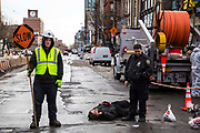 A man lies in the street talking on his phone after falling off his bike, an NYPD police officer stands next to him and workman holds a SLOW sign to control the traffic on East Houston Street in Lower East Side, New York City, New York, Unites States of America.