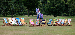 © Licensed to London News Pictures. 04/07/2013. London, UK. Tetua, a 13 year old Portugese Lusitano horse, is posed and painted to match a deckchair designed by Rolling Stones musician Ronnie Wood (centre) amongst others created by artists and celebrities at the press launch for Deckchair Dreams 2013 in Hyde Park, London, today (04/07/2013).  The 16 designer limited edition deckchairs, part of a public art initiative run by the Royal Parks Foundation, will go on sale with all proceeds going to work inside the parks.  Photo credit: Matt Cetti-Roberts/LNP