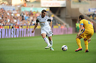 Angel Rangell of Swansea City is tackled by Guilherme of Petrolul Ploiesti.<br /> UEFA Europa league, play off round, 1st leg match, Swansea city v FC Petrolul Ploiesti at the Liberty stadium in Swansea on Thursday 22nd August 2013. pic by Phil Rees , Andrew Orchard sports photography,