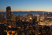 """Downtown Seattle, the Space Needle, Puget Sound and the Olympic Mountains at sunset, on July 4, 2007. Published in """"Light Travel: Photography on the Go"""" book by Tom Dempsey 2009, 2010. Photographed by Tom Dempsey from the 33rd floor of First Hill Plaza, 1301 Spring Street, Seattle, Washington."""