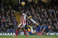 Gary Cahill of Chelsea challenges Stoke City's Saido Berahino (L)as he attempts an aerial interception. <br /> Premier league match, Chelsea v Stoke city at Stamford Bridge in London on Saturday 30th December 2017.<br /> pic by Kieran Clarke, Andrew Orchard sports photography.