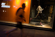 Jogger runs past Nike shop window in central London. It is almost dark on this evening in the city and a runner passes the Nike shop in London's Covent Garden. Echoing the shop mannequin that has been placed carefully in a classic athlete's position, they both stride from left to right in the darkening street. Nike is one of the world's largest suppliers of athletic shoes and apparel and a major manufacturer of sports equipment, with revenue in excess of US$24.1 billion in its fiscal year 2012 (ending May 31, 2012). As of 2012, it employed more than 44,000 people worldwide. In 2014 the brand alone was valued at $19 billion, making it the most valuable brand among sports businesses.