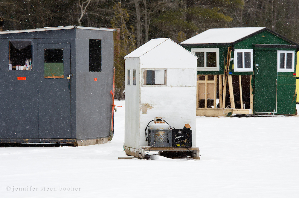 Three ice-fishing huts in Acadia National Park, Maine. The green one was damaged when it fell through the ice.