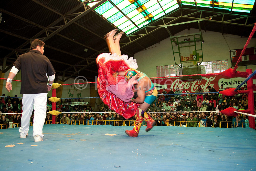 Alicia Flores female wrestler in the ring wrestling a male opponent, being slammed down with crowd in background. Lucha Libre wrestling origniated in Mexico, but is popular in other latin Amercian countries, including in La Paz / El Alto, Bolivia. Male and female fighters participate in the theatrical staged fights to an adoring crowd of locals and foreigners alike.
