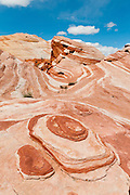 "The ""Fire Wave"" is a one mile round trip walk in the White Domes area of Valley of Fire State Park, the oldest state park in Nevada (dedicated in 1935). Starting more than 150 million years ago, great shifting sand dunes during the age of dinosaurs were compressed, uplifting, faulted, and eroded to form the park's fiery red sandstone formations. The park also boasts fascinating patterns in limestone, shale, and conglomerate rock. The park adjoins Lake Mead National Recreation Area at the Virgin River confluence, at an elevation of 2000 to 2600 feet (610-790 m), 50 miles (80 km) northeast of Las Vegas, USA. Park entry from Interstate 15 passes through the Moapa Indian Reservation."